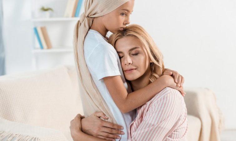 Niña con cáncer abrazando a su madre