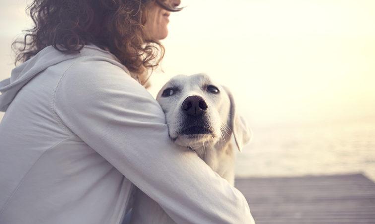 Una mujer y su perro, abrazados (Istock)